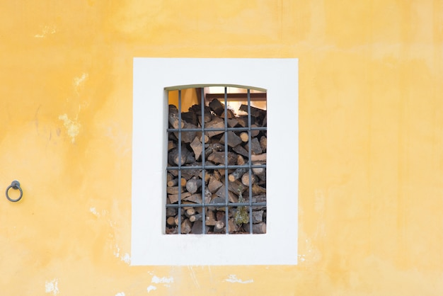 Fire wood in square cage on the yellow rustic wall