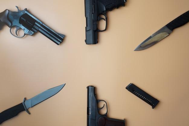 원을 따라 배치 된 총기. 중립 베이지 색 배경에 3 개의 총 권총, 카트리지, 육군 칼 클로즈업.