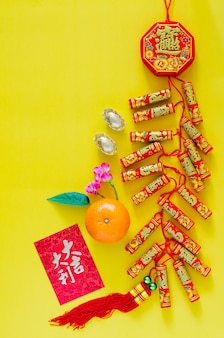 Firecrackers for chinese new year ornament (word means wealth, blessing) with gold ingots, orange and red envelope packet or ang bao (word means auspice) on yellow background.