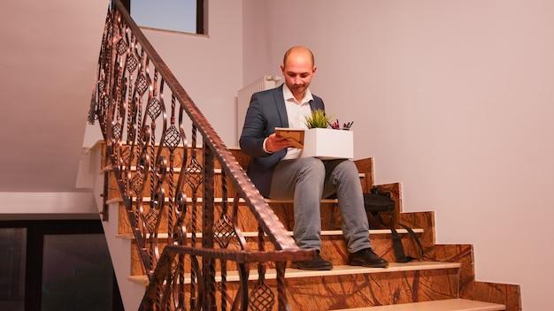 Уволенный бизнесмен сидит на лестнице в компании корпоративных финансов, холдинг коробку личных вещей сотрудника. группа профессиональных успешных бизнесменов, работающих в современном финансовом здании.