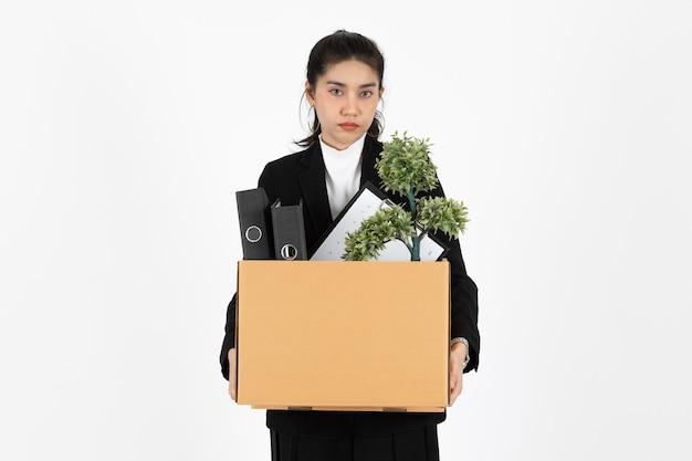 Уволенная молодая азиатская бизнес-леди держит коробку с личными вещами