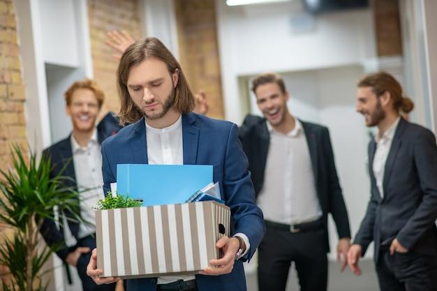Уволенный сотрудник в деловом костюме с коробкой личных вещей идет по коридору и тремя смеющимися мужчинами.