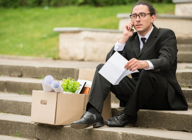 Fired frustrated man in suit sitting near office at stairs.