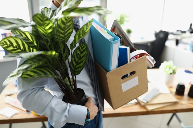 The fired man carries personal belongings and a flower in a box unexpected dismissal concept