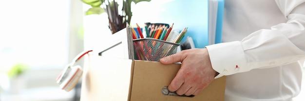 Уволенный человек, несущий коробку с личными вещами