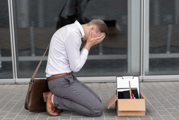 The fired office worker fell to his knees and covered his face due to stress.