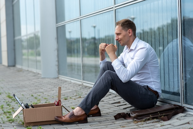 A fired office worker sits on the floor near a modern office building. the man is very worried about the dismissal. the employee is very angry.