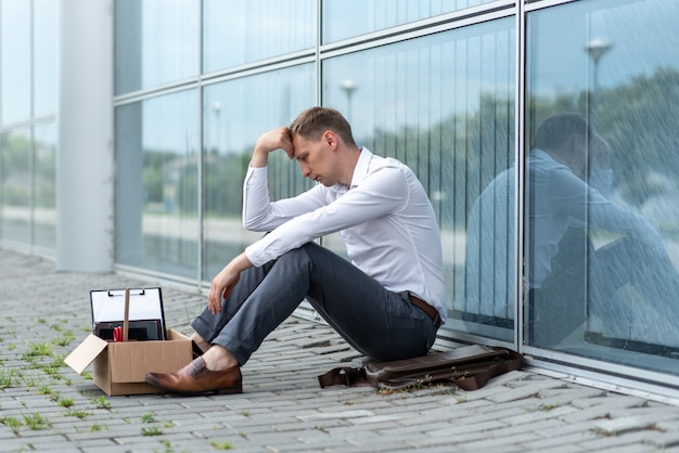 A fired office worker sits on the floor near a modern office building. the man is very worried about the dismissal.