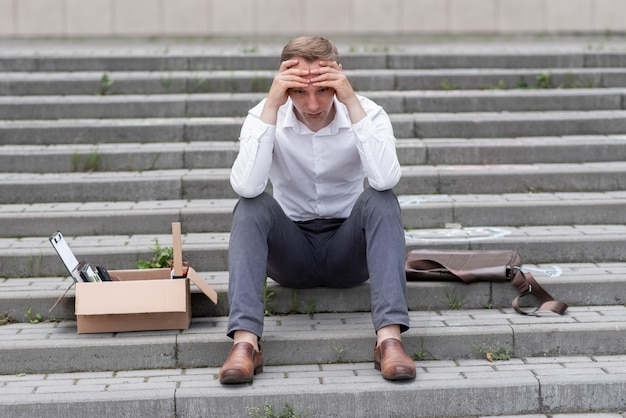 A fired office worker sits on the steps. the man does not know what to do next. next to it is a cardboard box with stationery.