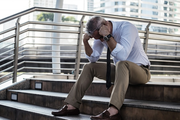 Fired sad businessman sitting on stairs