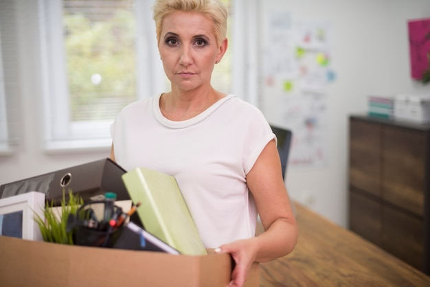 Fired woman carrying a box with some content