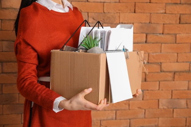 Fired woman with personal stuff on brick wall