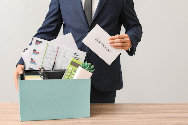 Fired worker with personal things at table