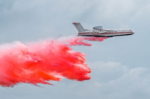 Firefighter airplane drops red water on a fire in the forest.