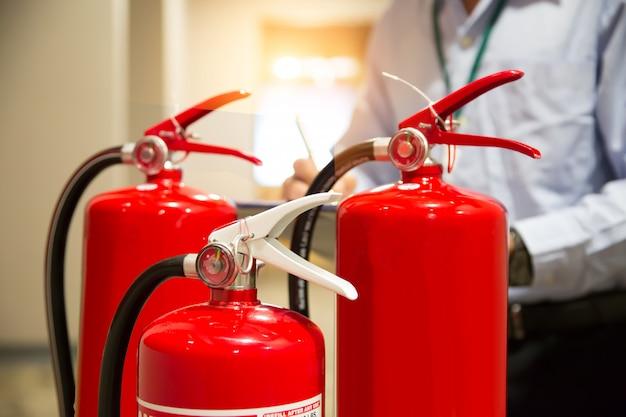 消防士が消火の建物のコンセプトで消火器タンクをチェック