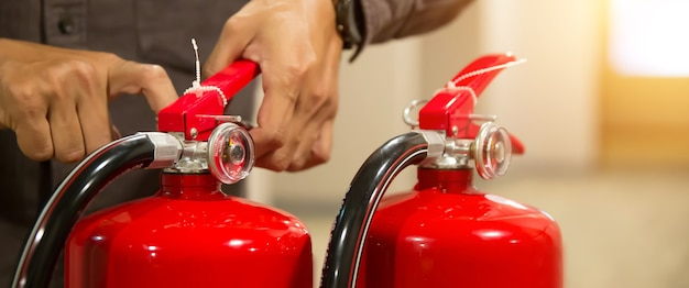 Firefighter checking the safety pin at handle of fire extinguisher.