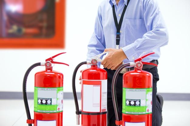 Пожарный проверяет ручку красного бака огнетушителей.