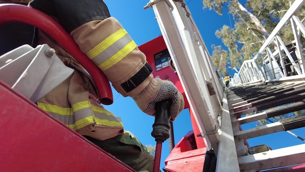 Firefighter doing tree rescue on top of ladder truck.