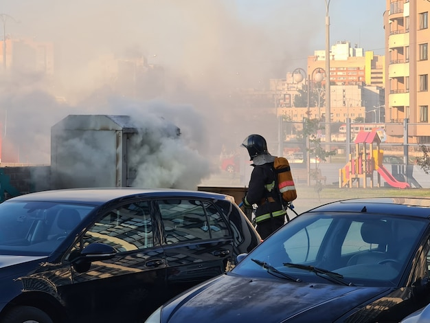 家の庭で燃えているゴミ箱を消火する消防士