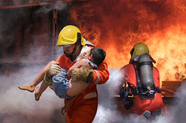 Firefighter holding child boy to save him in fire and smoke.