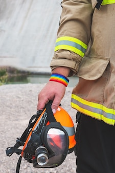 Firefighter holding helmet, with lgbt bracelet. vertical photo