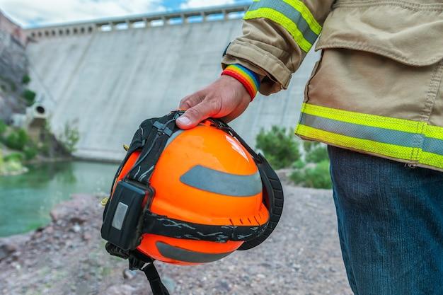 Firefighter holding helmet, with lgbt bracelet.