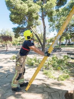 Пожарный держит лестницу руками