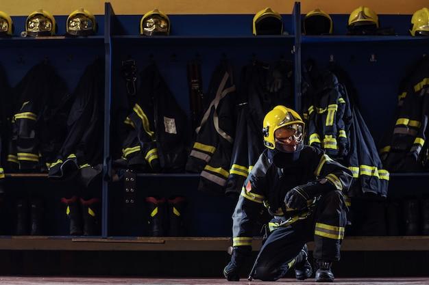 保護服を着た消防士がひざまずいて頭に手袋をはめ、行動の準備をしています。
