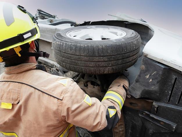 소방관이 추락 한 차량의 바퀴 주위에 슬링을 배치합니다.