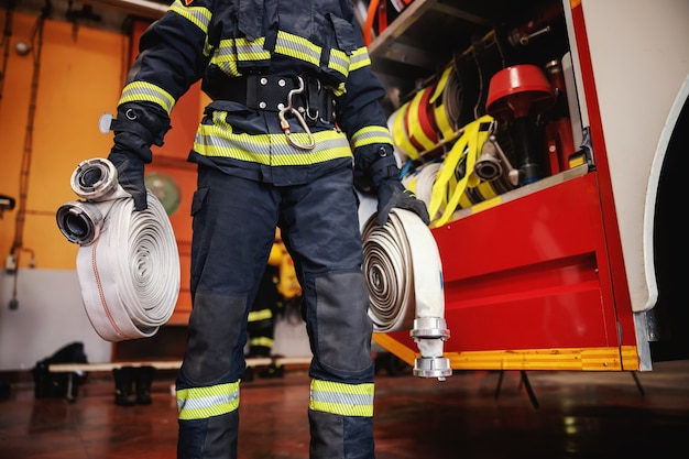 Firefighter in protective uniform with helmet on head checking on hoses before intervention while standing in fire station.