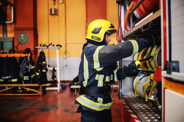 Firefighter in protective uniform with helmet on head checking on hoses before intervention while standing in fire station