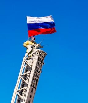 Пожарный охраняет российский флаг на пожарной лестнице на голубом небе