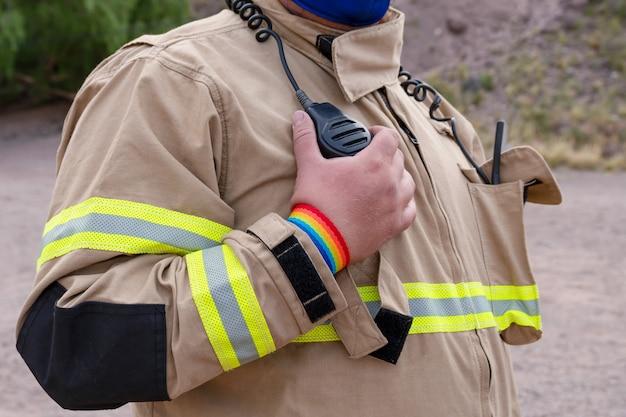 Firefighter speaking by handy, with lgbt bracelet.