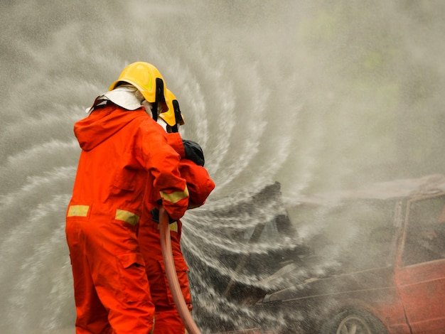 Firefighter spray water to fire burning car workshop fire training