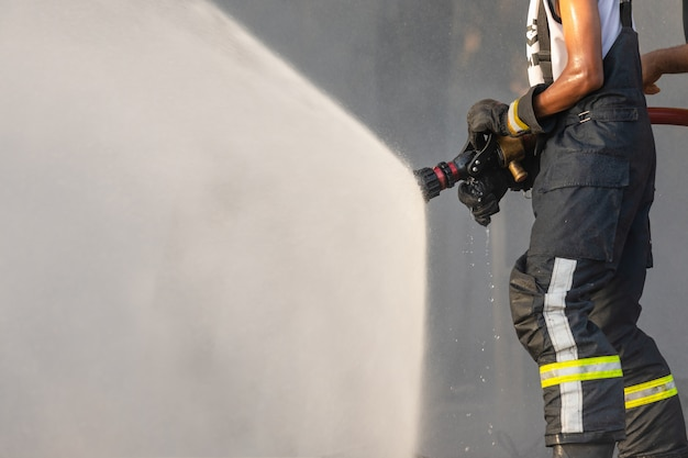 Firefighter spraying water from big water hose to prevent fire