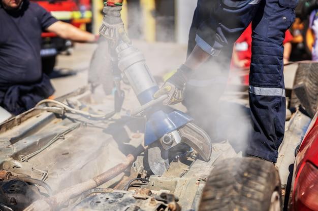 墜落した車の上に立って、車の中で人を解放しようとしている消防士。