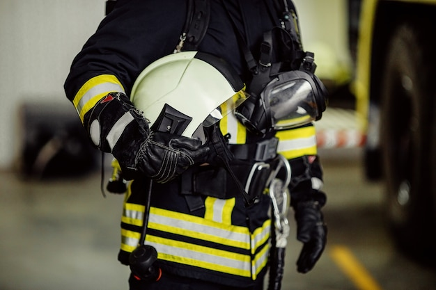 Firefighter in uniform with gas mask and helmet near fire engine