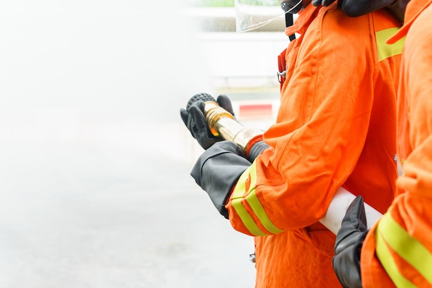 Firefighter using extinguisher and water from hose for fire fighting
