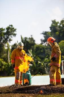消防士を訓練するための消防士を守るための火とスーツを持つ消防士。
