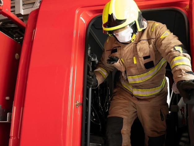 介入スーツを装備したトラックから降りるマスク付き消防士