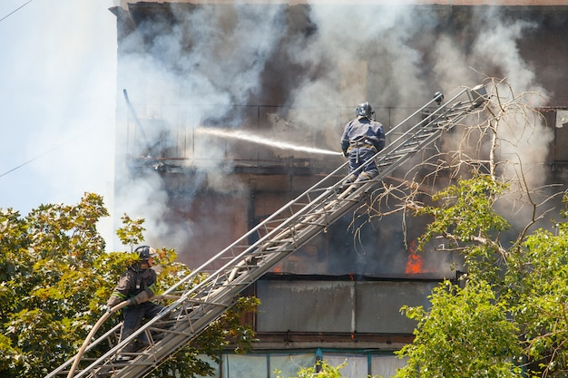 Firefighters extinguish a fire in a high-rise residential building.