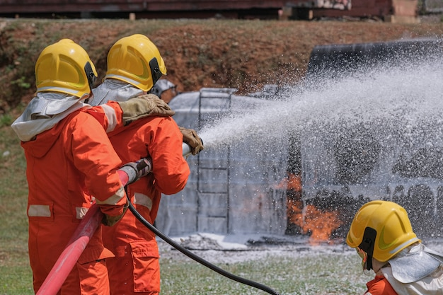 Firefighters extinguish the fire with a chemical foam coming from the fire engine through a long hose.