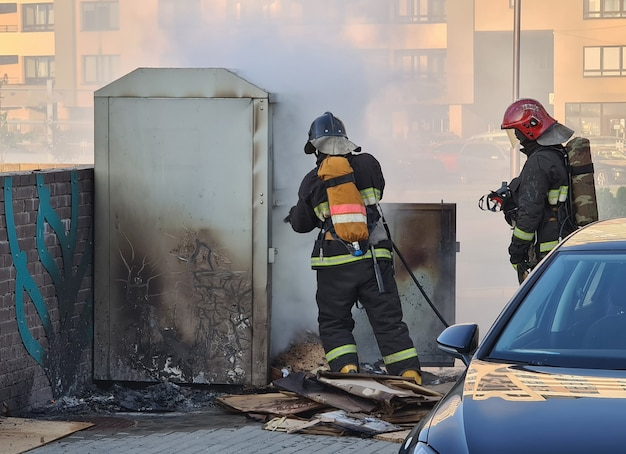 Firefighters extinguishing garbage can fire in car park