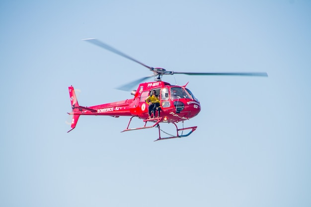 Firefighters helicopter in rio de janeiro, brazil - april 24, 2021: firefighters helicopter flying over copacabana beach in rio de janeiro.