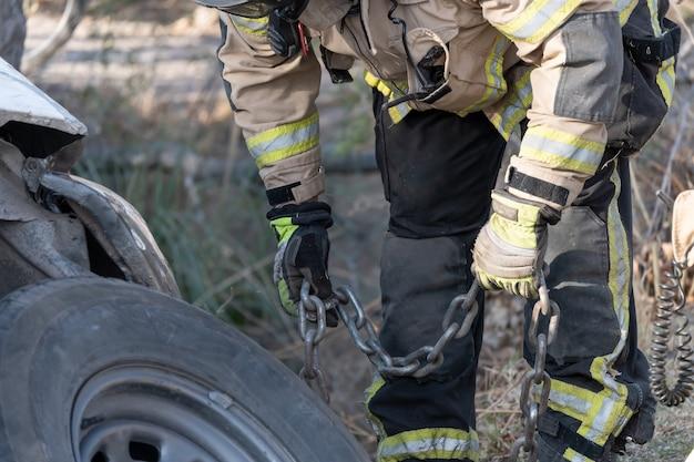消防士が溝に落ちた車を救助します。
