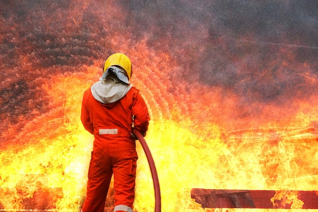消防士の訓練、緊急事態での消防へのチーム練習。消防士が炎の中を通る水ホースを運ぶ