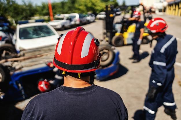 墜落した車の中で人を解放しようとしている消防士。