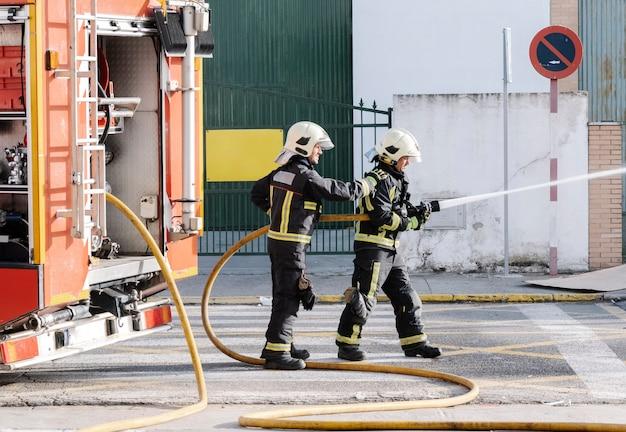 Пожарные с водным шлангом, тянущим воду, чтобы тушить пожар