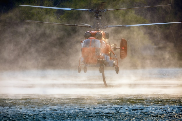 Firefighting helicopter is hovering over the pond to refills water