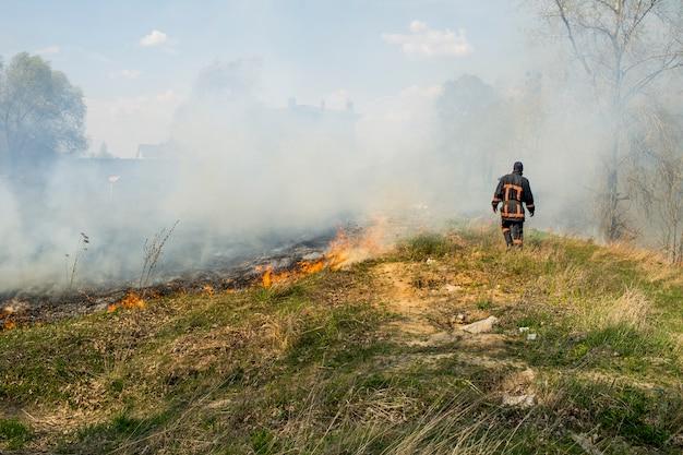 火の背景に消防士、春の草や小枝で燃える山火事